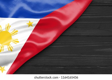 Flag of the Philippines and place for text on a dark wooden background