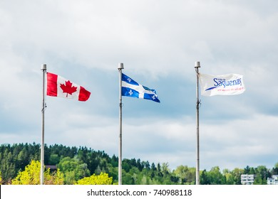 Flag poles with Quebec, Canadian and Saguenay symbols against sky in wind