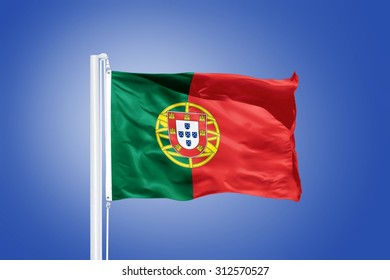 Flag of Portugal flying against a blue sky.