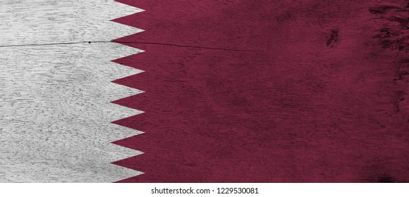 Flag of Qatar on wooden plate background. Grunge Qatari flag texture, a white band on the hoist side, separated from a maroon area on the fly side by nine white triangles.