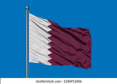 Flag of Qatar waving in the wind against deep blue sky. Qatari flag.