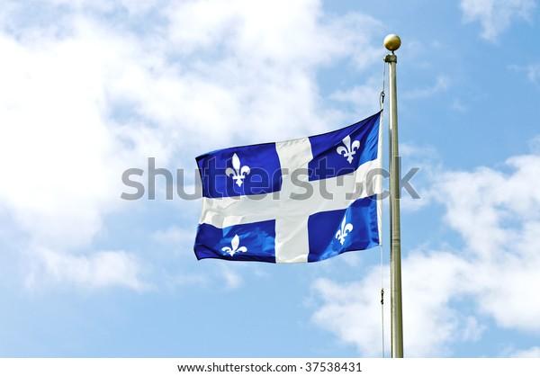Drapeau du Québec contre le ciel bleu.