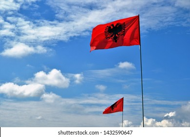 Flag Republic of Albania. Albanian flag on a flagpole waving on a blue sky. Albanian red flag with a black double-headed eagle in the centre