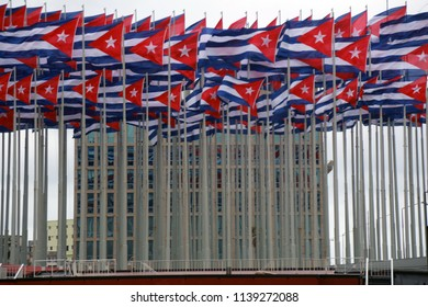 The flag of the Republic of Cuba hoisted in front of the American Embassy on the Malecon seafront and waves covering its visual Havana Cuba January 2014