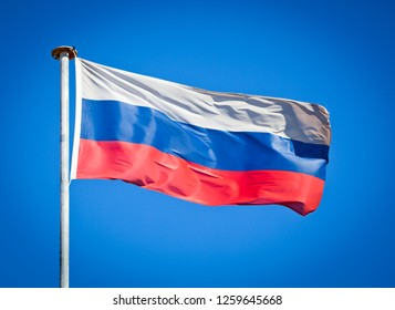 Flag of Russia. Flag blowing in strong wind against pure blue sky. Tricolour, symbol of national patriotism.