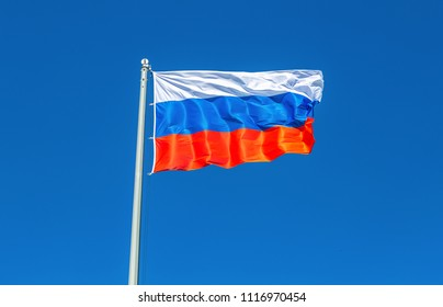 Flag of Russia waving in the wind against the blue sky