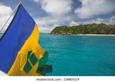 Flag of Saint Vincent and the Grenadines hangs off the stern of a sailing ship in the Tobago Cays