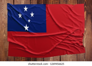 Flag of Samoa on a wooden table background. Wrinkled Samoan flag top view.