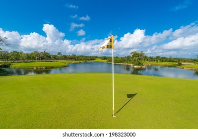 Flag and sand bunkers and a lake as a background at the beautiful golf course of the luxury Mexican resort.