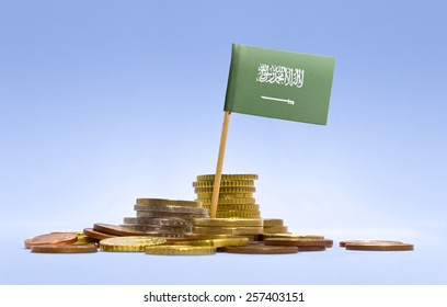 Flag of Saudi Arabia in a mixed stack of european coins and a blue background.(series)