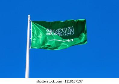 Flag of Saudi Arabia waving in the wind against the blue sky