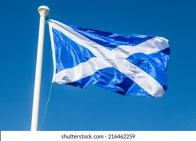 Flag of Scotland on blue sky background ona windy day