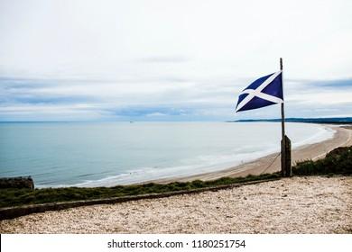 Flag of Scotland on the sea background. St Cyrus beach, Angus, Aberdeenshire, Scotland, UK