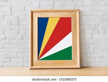 Flag of Seychelles on photo frame. Seychelles Flag in wooden frame.