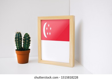 Flag of Singapore on photo frame. Singapore Flag in wooden frame.