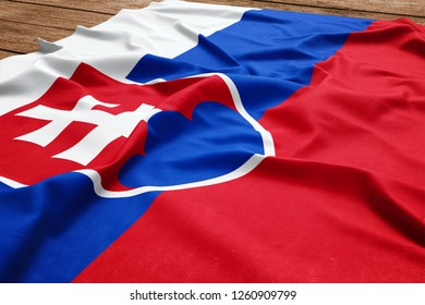 Flag of Slovakia on a wooden desk background. Silk Slovak flag top view.
