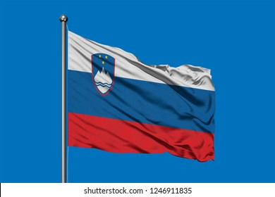 Flag of Slovenia waving in the wind against deep blue sky. Slovenian flag.