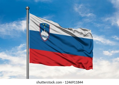 Flag of Slovenia waving in the wind against white cloudy blue sky. Slovenian flag.