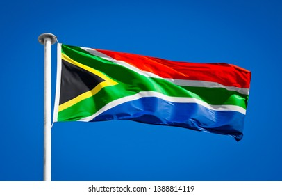 Flag of South Africa blowing in strong wing against pure blue sky. Symbol of national patriotism.