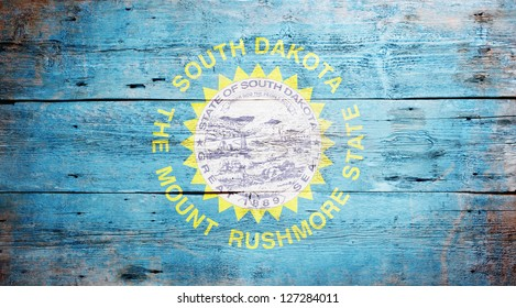 Flag of South Dakota painted on grungy wooden background