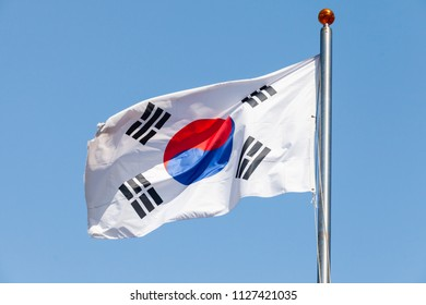 Flag of South Korea, also known as the Taegukgi waving on a flagpole over blue sky background