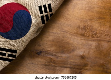 Flag of South Korea made from rough fabric on a wooden background.