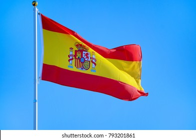 Flag of Spain fluttering in the breeze against a bright blue sky. The flag is red and yellow with a coat of arms in the yellow center. The flag is called Pandera de Espania