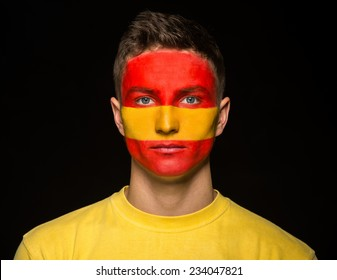 Flag of Spain painted on a face of a young man.