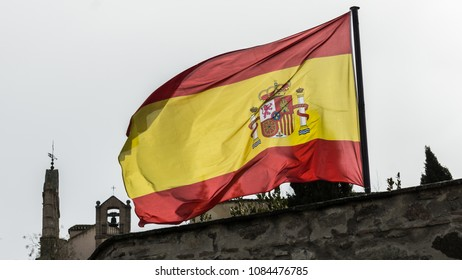 Flag of Spain under the cloudy grayish winter sky and with the detail of a church in the background.