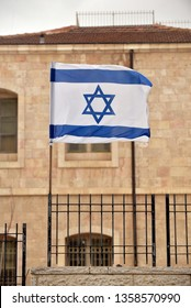 The flag of the State of Israel with the Star of David in front of a building in Jerusalem.
