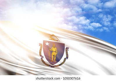 flag of State of Massachusetts against the blue sky with sun rays