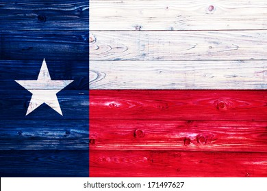The Flag of the State of Texas on a weathered natural wooden surface close-up