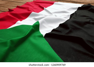 Flag of Sudan on a wooden desk background. Silk Sudanese flag top view.