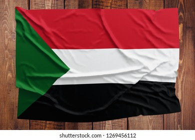 Flag of Sudan on a wooden table background. Wrinkled Sudanese flag top view.