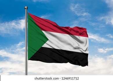 Flag of Sudan waving in the wind against white cloudy blue sky. Sudanese flag.
