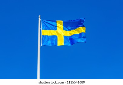 Flag of Sweden flying in the wind against the blue sky
