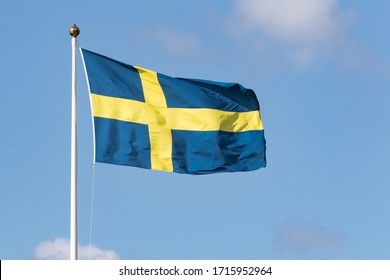 Flag of Sweden on flagpole waving in the wind on a beautiful sunny day with blue sky