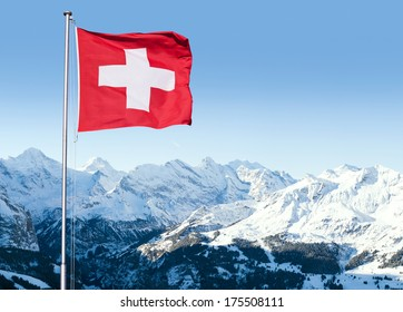 The flag of Switzerland fluttering in the wind with the Bernese Alps in the background.