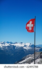 Flag of switzerland in front of mountains of the alps