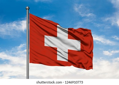Flag of Switzerland waving in the wind against white cloudy blue sky. Swiss flag.