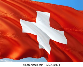 Flag of Switzerland waving in the wind against deep blue sky. High quality fabric.