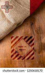 Flag  and symbol made in Malta on a wooden surface