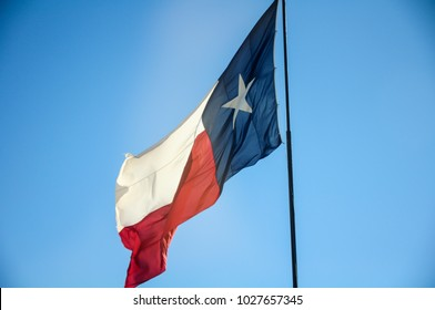 The flag of Texas high up in the sky.
