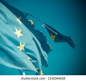 Flag is torn off at side, symbol of problems, decay, disintegration, decomposition, breakdown. European union twelve star flag torn and with knots in wind on blue sky background, close up