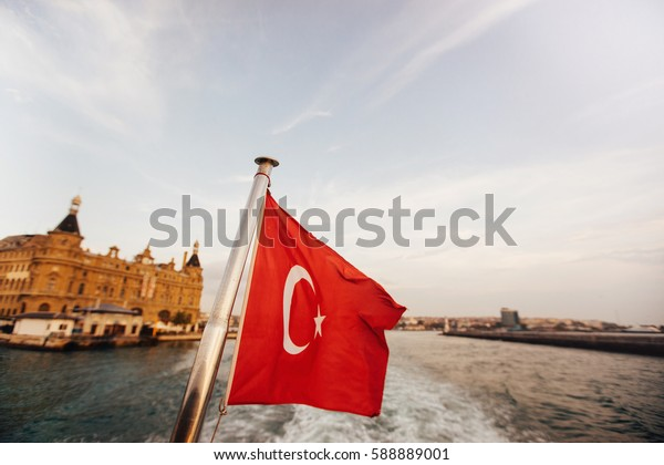 Flag of Turkey and lifebuoy on back of a boat in Bosphorus strait, Istanbul, Turkey. Waves from the boat, the sea