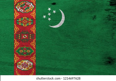 Flag of Turkmenistan on wooden plate background. Grunge Turkmenistan flag texture, green field with red stripe containing five carpet guls above two olive branches; crescent and stars.