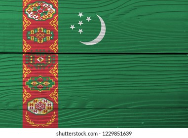Flag of Turkmenistan on wooden plate background. Grunge Turkmen flag texture, green field with red stripe containing five carpet guls stacked above two crossed olive branches; crescent and stars.
