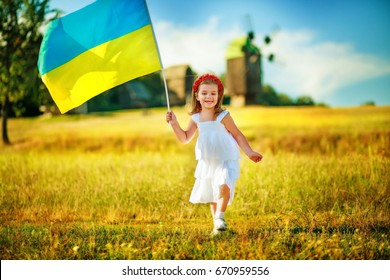 Flag Ukraine in hand little girl in wreath of red poppies. Child carries fluttering blue and yellow flag of Ukraine against background of mills in Pirogovo.