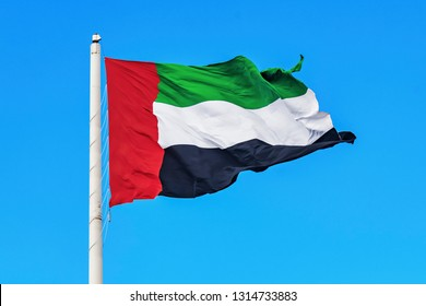 Flag of the United Arab Emirates, UAE waving during a clear blue sky.