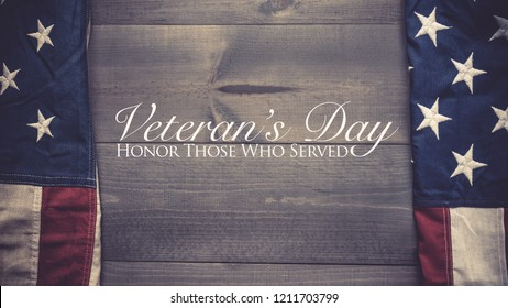 The flag of the United Sates of America on a grey plank background with Veterans Day greeting